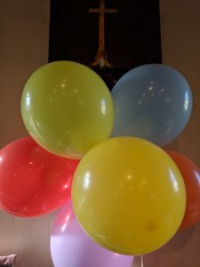 Picture of colourful balloons under a cross